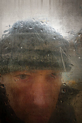 Man looking through dirty glass window - p597m793875 by Tim Robinson