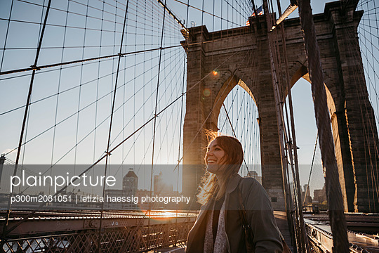 USA, New York, New York City, female tourist on Brooklyn Bridge at sunrise - p300m2081051 by letizia haessig photography