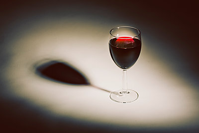 Glass full of red wine against white background - p1057m1564501 by Stephen Shepherd