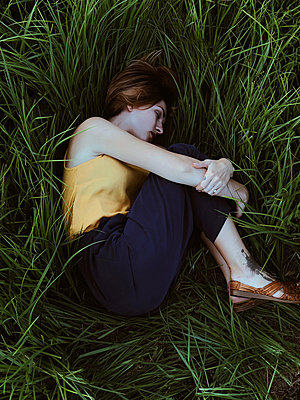 View from above of young woman lying down on a green grass. - p1166m2112042 by Cavan Images