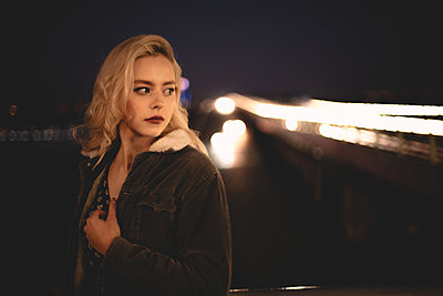Portrait of young woman standing against illuminated bridge in city - p1166m2153570 by Cavan Images