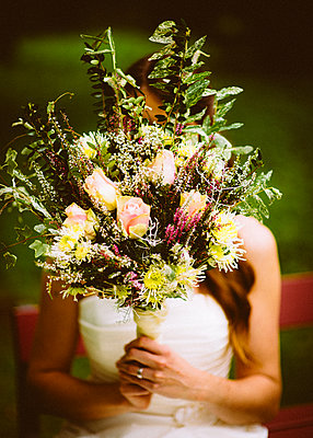 Bride holding big bouquet of flowers - p1616m2187740 by Just - Schmidt