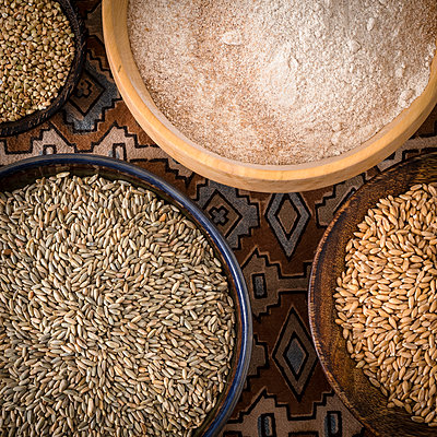 Bowls of spelt grains, rye grains, buckwheat grains and whole grain wheat flour - p300m1023389f by Dieter Schewig