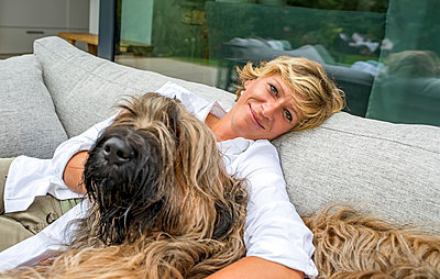 Portrait of woman relaxing with dog on terrace at home - p300m2155530 by Bernd Friedel