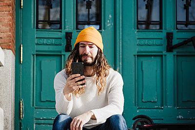 Handsome man using smart phone in front of wooden door - p300m2274715 by Eva Blanco