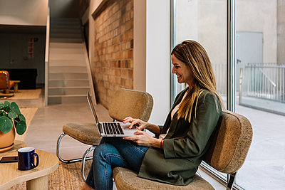 Smiling businesswoman using laptop while sitting on chair at office - p300m2276767 by Xavier Lorenzo