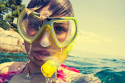 Croatia, Brac, Sumartin, Teenage girl in water with diving goggles and snorkel - p300m980517f by Dieter Schewig