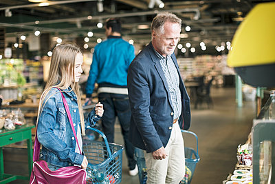 Father and daughter buying groceries at supermarket - p426m1407394 by Kentaroo Tryman