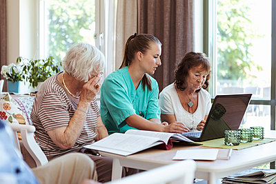 Healthcare worker and elderly women with laptop and medical reports at nursing home - p426m2072586 by Kentaroo Tryman