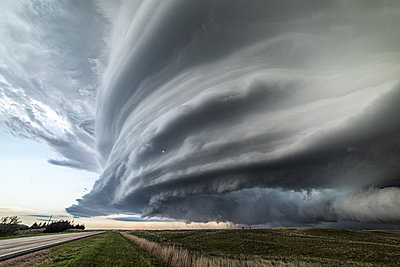 Sculpted super-cell, a mesocyclone weather formation thunderstorm clouds, drifting majestically across the Nebraska sand hills. - p924m2196800 by Jessica Moore