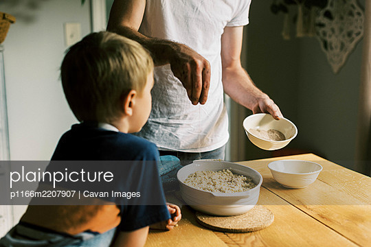 A father and son putting a cinnamon sugar mixture on a peach cobbler - p1166m2207907 by Cavan Images
