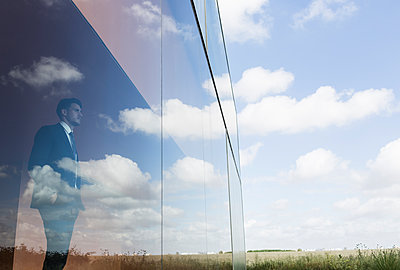 Pensive businessman looking out modern office window at blue sky and clouds - p1023m1519840 by Martin Barraud