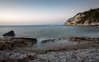 Deserted Greek seaside cove at dusk with smooth sea, rocks and pebbly beach. - p1433m1529107 by Wolf Kettler