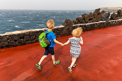 High angle view of siblings holding hands while running on pier by sea at Costa Adeje, Canary Islands, Spain - p300m2198382 by Irina Heß