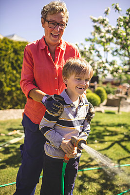 Happy grandmother and grandson spraying water in yard - p426m1468454 by Maskot