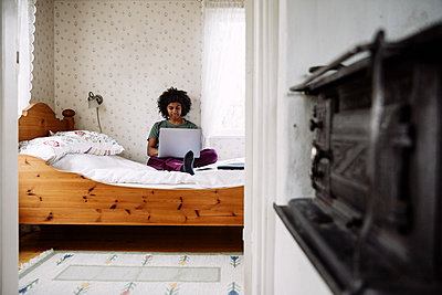 Young woman using laptop while relaxing on bed at home seen through doorway - p426m2117146 by Maskot