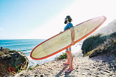 Caucasian man holding surfboard at beach - p555m1304647 by Peathegee Inc