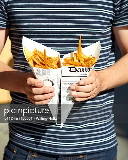 Mann hält zwei Tüten Pommes Frites  - p1124m1150031 von Willing-Holtz