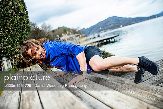Athlete exercising at lakeshore - p300m1581725 von Daniel Waschnig Photography