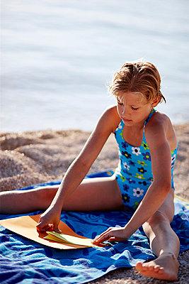 Mädchen am Strand bastelt ein Boot aus Papier - p1026m834446 by Secen-Steets