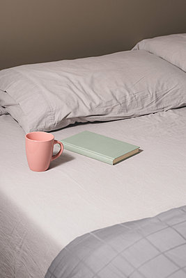 Cup and book placed on bed - p1165m1195422 by Pierro Luca