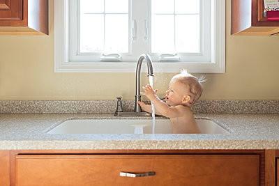 Shirtless baby boy playing with water while sitting in kitchen sink - p1166m1543953 by Cavan Images