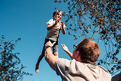Father throwing little son up in air - p300m2166938 by Wilfried Feder
