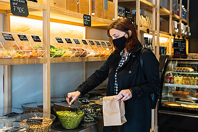 Woman wearing protective face mask buying green peas at supermarket during pandemic - p300m2286889 by NOVELLIMAGE
