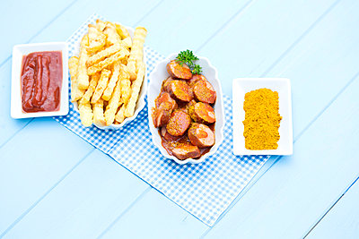 Bowl of sausages with french fries, currywurst and ketchup on wooden table, close up - p300m827389f by Roman Märzinger