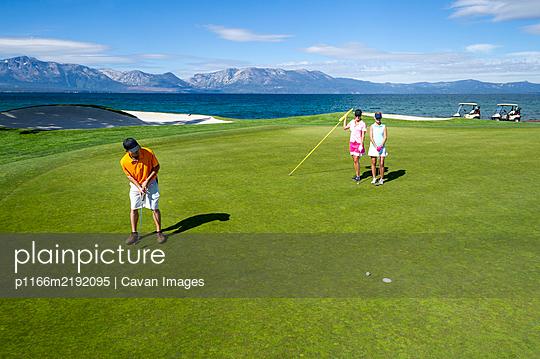 Three people playing golf at Edgewood Tahoe in Stateline, Nevada. - p1166m2192095 by Cavan Images