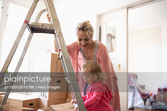 Mother and daughter at ladder, moving into new home - p1192m2016786 by Hero Images