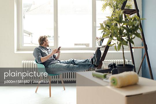 Man renovating room sitting on armchair having a break - p300m1581682 von Joseffson
