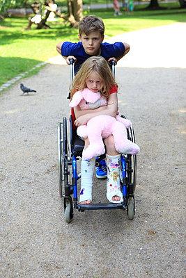 Bruder schiebt Schwester im Rollstuhl - p045m1064546 von Jasmin Sander