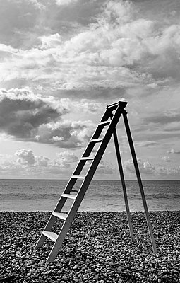 Ladder standing on pebble beach by the ocean, cloudy sky. - p1100m1570937 by Mint Images