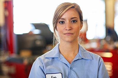 Portrait of young female Caucasian mechanic in auto repair shop - p1100m2248997 by Mint Images