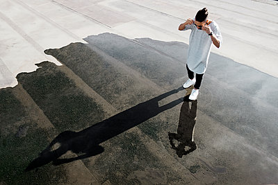 High angle view of man standing on puddle at street - p1166m1088402f by Aristos Iatrou