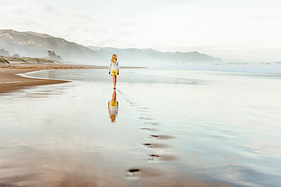 Preteen girl waling on beach in New Zealand - p1166m2129611 by Cavan Images