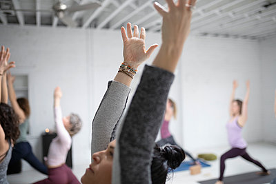 Women practicing yoga warrior one pose in yoga class - p1192m1583326 by Hero Images