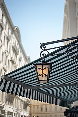 Lit street light by day under a stripy awning. - p1433m1573400 by Wolf Kettler