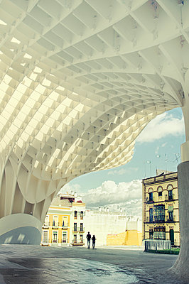 Couple walks past Metropol Parasol - p1445m2150462 by Eugenia Kyriakopoulou