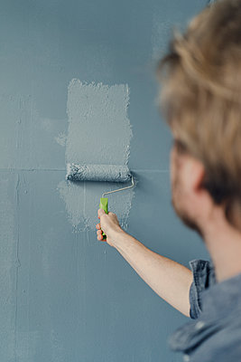 Man painting wall with paint roller - p300m1580775 by Joseffson