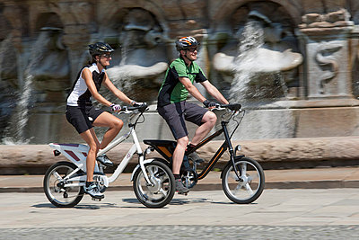 Man and woman riding electric bicycle - p300m660194f by Daniel Simon