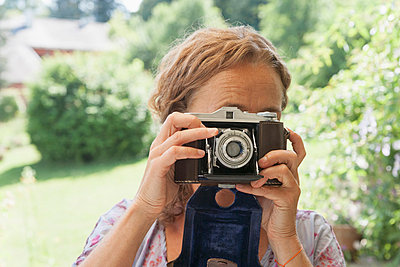Germany;  Bavaria;  Munich;  Mature woman taking picture with camera - p300m837028f by Tom Chance