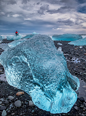 Blue ice on the shore of Jokulsarlon with a man standing on an iceberg in the distance, South coast; Iceland - p442m2003733 by Robert Postma