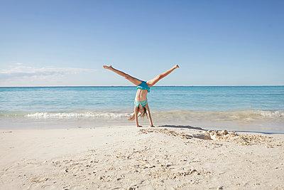 Caucasian girl doing cartwheel on beach - p555m1409655 by Shestock