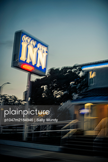 Driving past ocean park inn at night with vacancy sign showing red - p1047m2184946 by Sally Mundy
