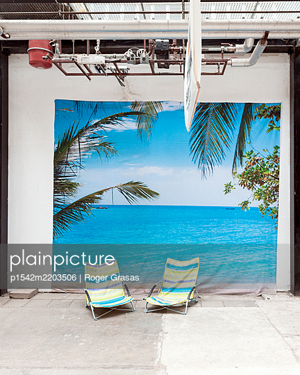 Tropical sea picture and beach chairs in a industrial building - p1542m2203506 by Roger Grasas