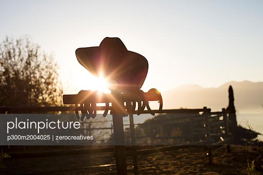 Cowboy hat in the sunset on a farm - p300m2004025 von zerocreatives