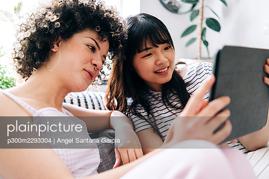 Smiling woman using digital tablet with female friend at home - p300m2293304 by Angel Santana Garcia