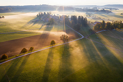 Germany, Bavaria, Ried near Dietramszell, ground fog at sunrise, drone view - p300m2081471 by Martin Siepmann